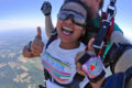 Woman gives a thumbs up during a tandem skydive she received as a gift.