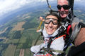 woman smiles at camera flyer under skydiving canopy