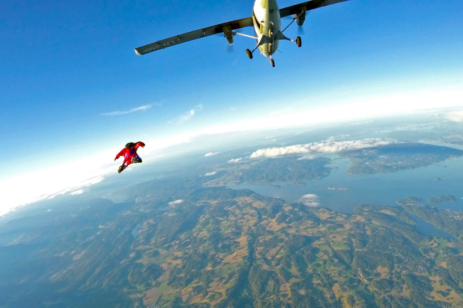 wingsuit flyer soars over beautiful landscape