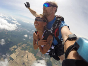 Tandem skydive with smiling girl, captured with GoPro