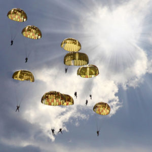 Military skydivers preparing for a parachute landing fall