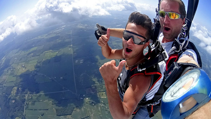 Young man hollering during a tandem skydive.