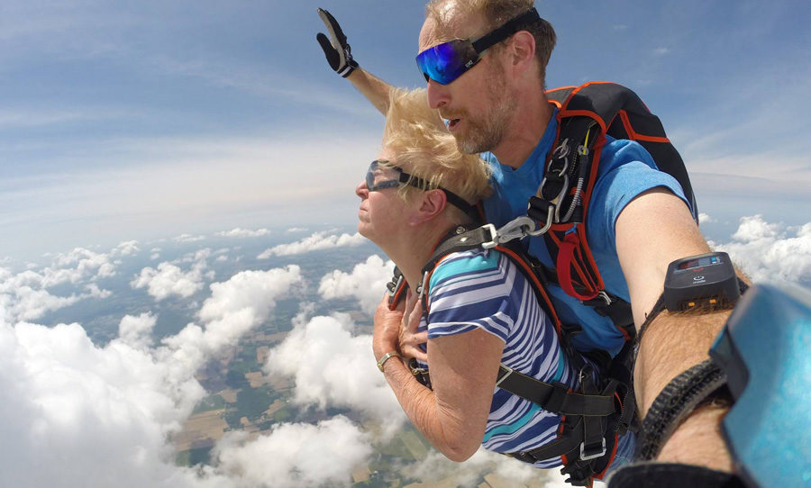 Older woman tandem skydiving with instructor