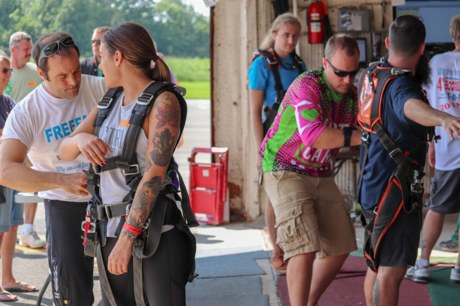 Fitting the tandem harness is part of how long skydiving lasts.