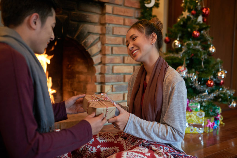 Happy woman receiving small Christmas gift - maybe a skydiving gift certificate?