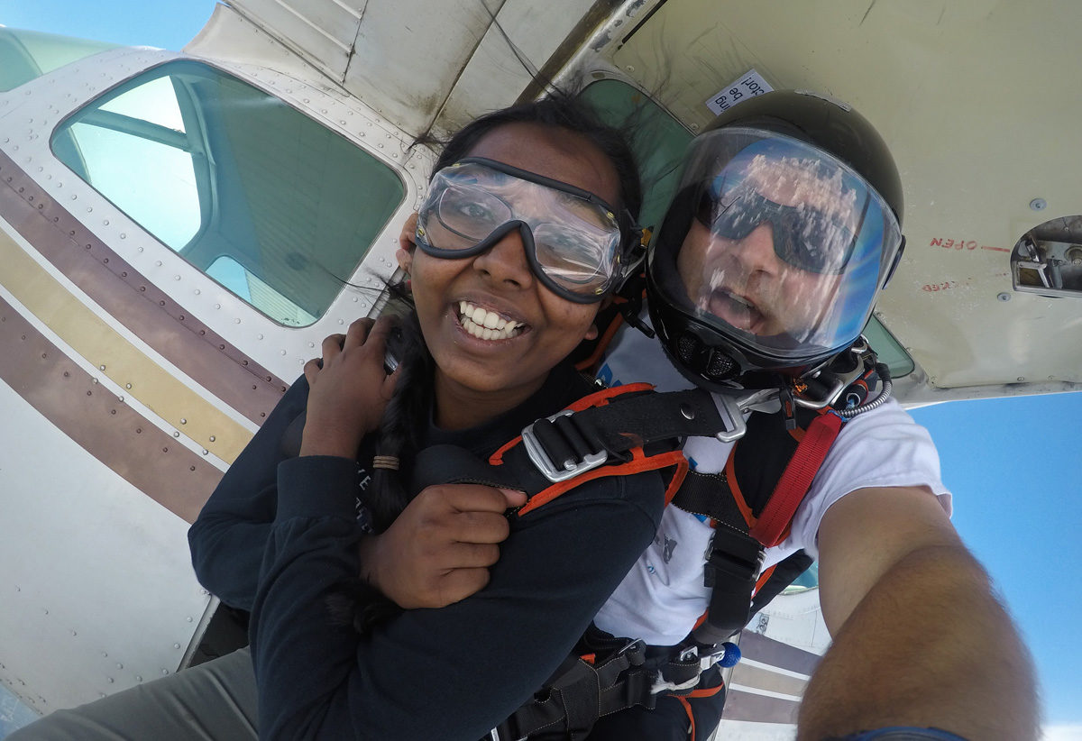 Young woman exits the plane on her first time tandem skydive