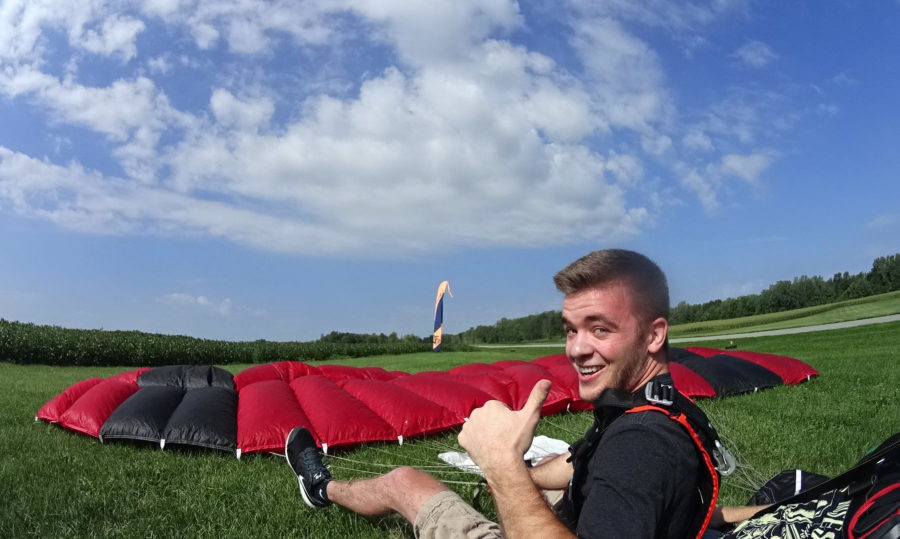 Skydiver giving thumbs up after landing in perfect weather.